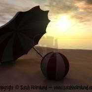 Sun parasol and beach ball on a beach at sunset